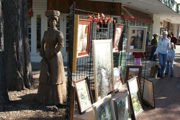 Paintings displayed along the brick sidewalks at Art in the Square, Tulsa