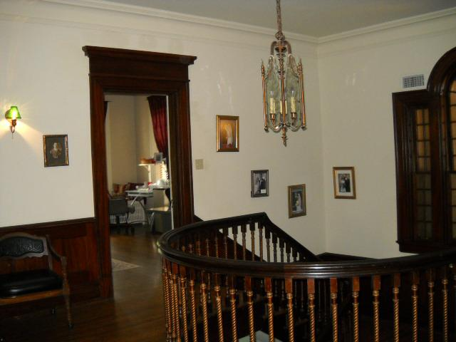 Grand staircase, wood flooring, high ceilings, crown moulding, stunning fixtures at the Kennedy Mansion Bed & Breakfast