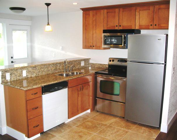 tops, stainless steel appliances, oak cabinets, bronze light fixtures