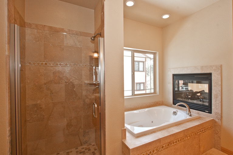 jetted tub, gas fireplace, shower, stone tiles