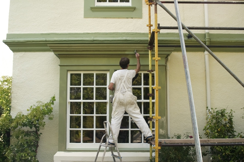 painter on a ladder painting the exterior of a home