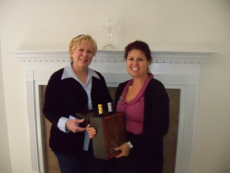 SouthAlabamaLiving Team Buyer Specialist, Nancy Sebastian, presents door price to Aspen Creek Resident, Laura Howell