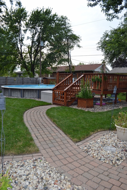 Backyard Pool withdeck brick paver patio and pathways to swingset and sitting are under tree and fire pit