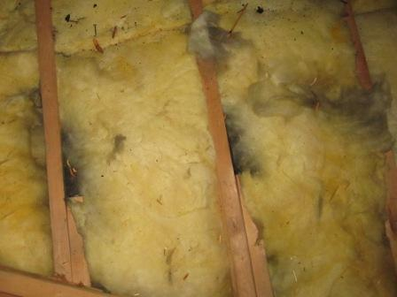 Black smudges on fiberglass insulation show air by passes into this Connecticut attic