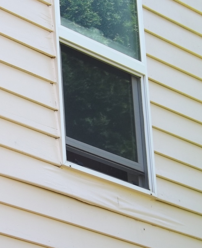 Paint failure and moisture intrusion around a vinyl window