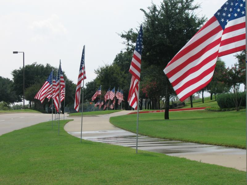 Many U.S. flags along street in front of Stonebridge United Methodist Church