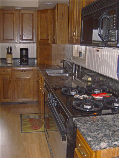 Bright%20custom%20kitchen%20with%20granite%20counters%2C%20gas%20cooking%2C%20microwave%20and%20dishwasher.