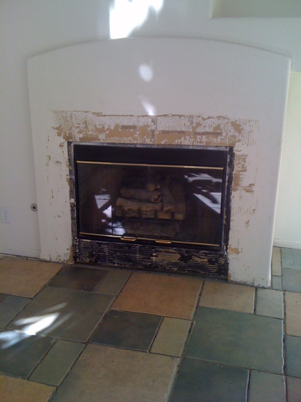 Fireplace, missing tiles, white walls inside a house