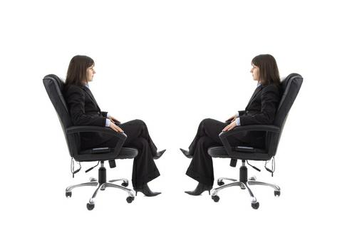 Mirror image woman in chair