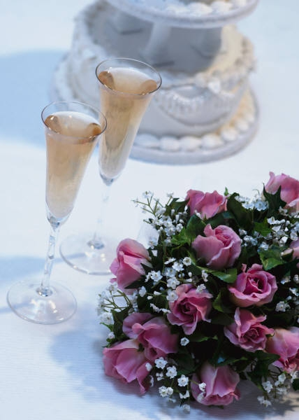 Table at a wedding reception with a wedding cake flowers and champagne