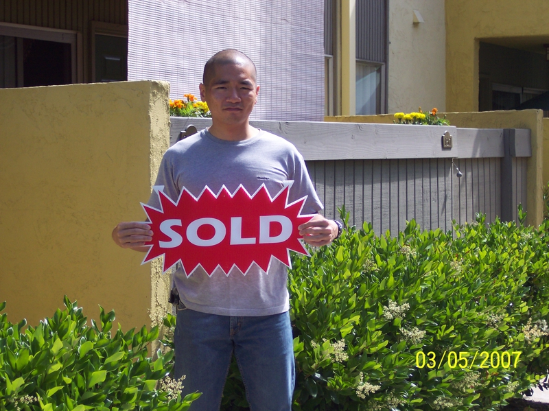 asian man holding red and white sold sign