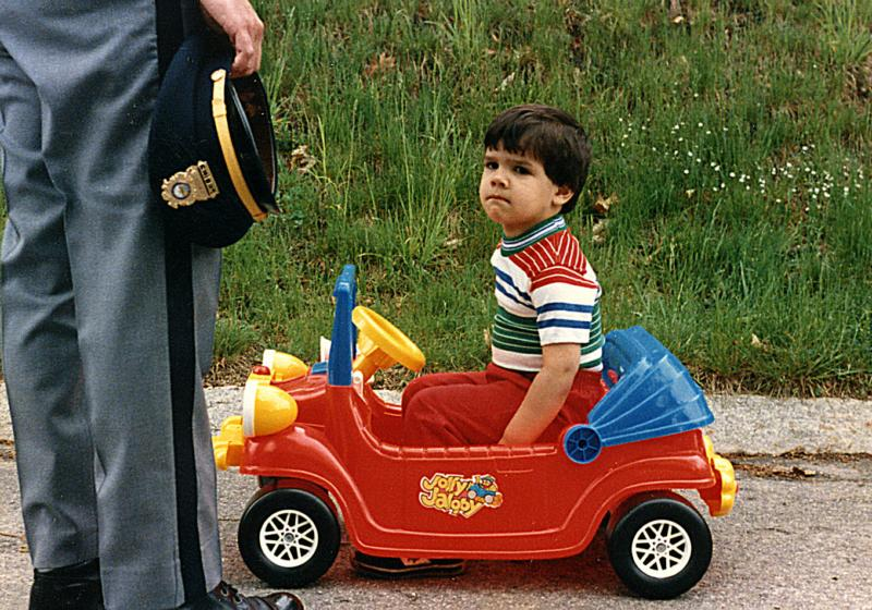 boy in toy car with officer standing by