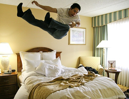 Guy bouncing on a Bed