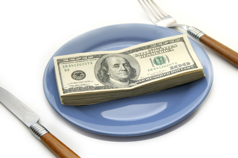 blue plate with 100 dollar bills and knife and fork
