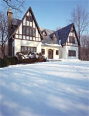 brown and white tudor in snow scene