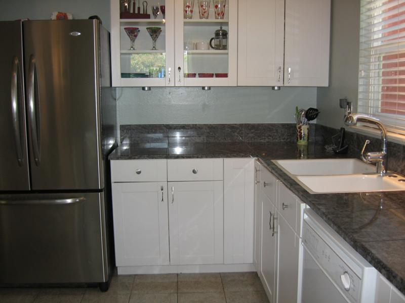 Remodeled kitchen with granite counters, white cabinets, gas cooktop