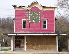 Run-down abandoned pink building with big questionmark on it