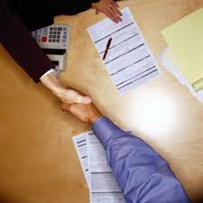 two people shaking hands over a table with paper and a calculator and contract