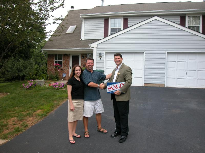Roy Giordano and a happy client holding a sold sign