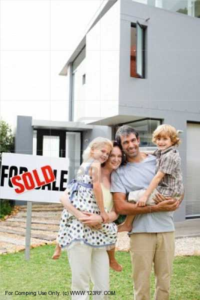 family of four standing in front of a house for sale