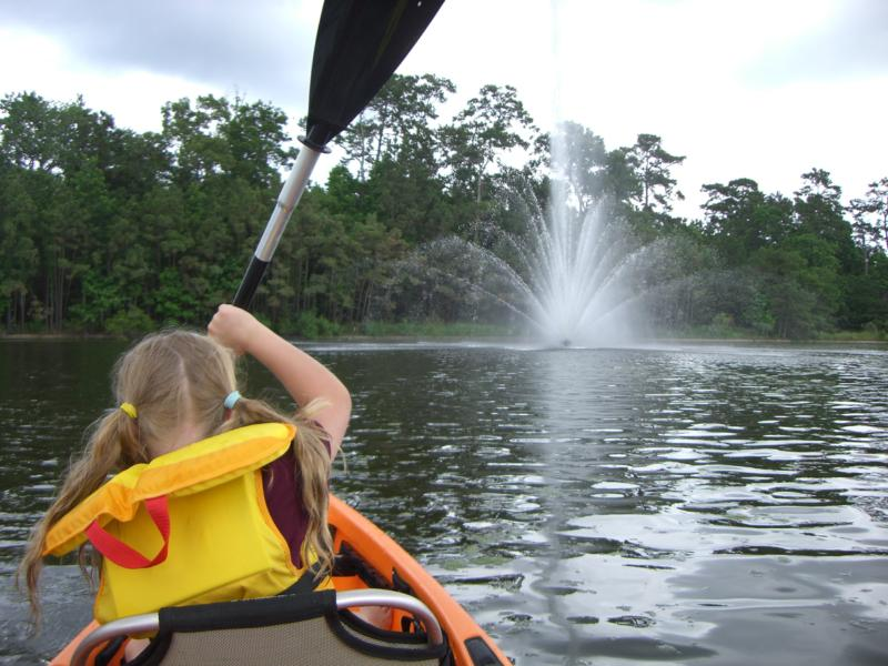 kayaking towards water fountain on lake woodlands the woodlands texas