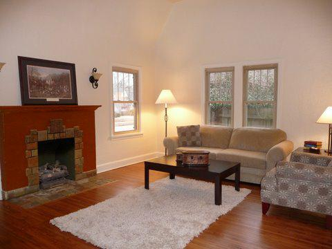 Art deco fireplace and wrought iron schones in Great Room of Florence Park bungalow for sale