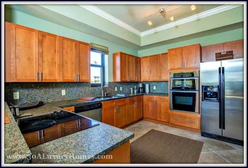 The lovely open kitchen in this condo for sale in Santa Rosa Beach FL has stainless steel appliances, granite counter tops, custom wood cabinets, tile backsplash and a breakfast bar will definitely inspire you to whip up delicious meals!
