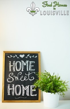 Home Sweet Home sign next to a houseplant.