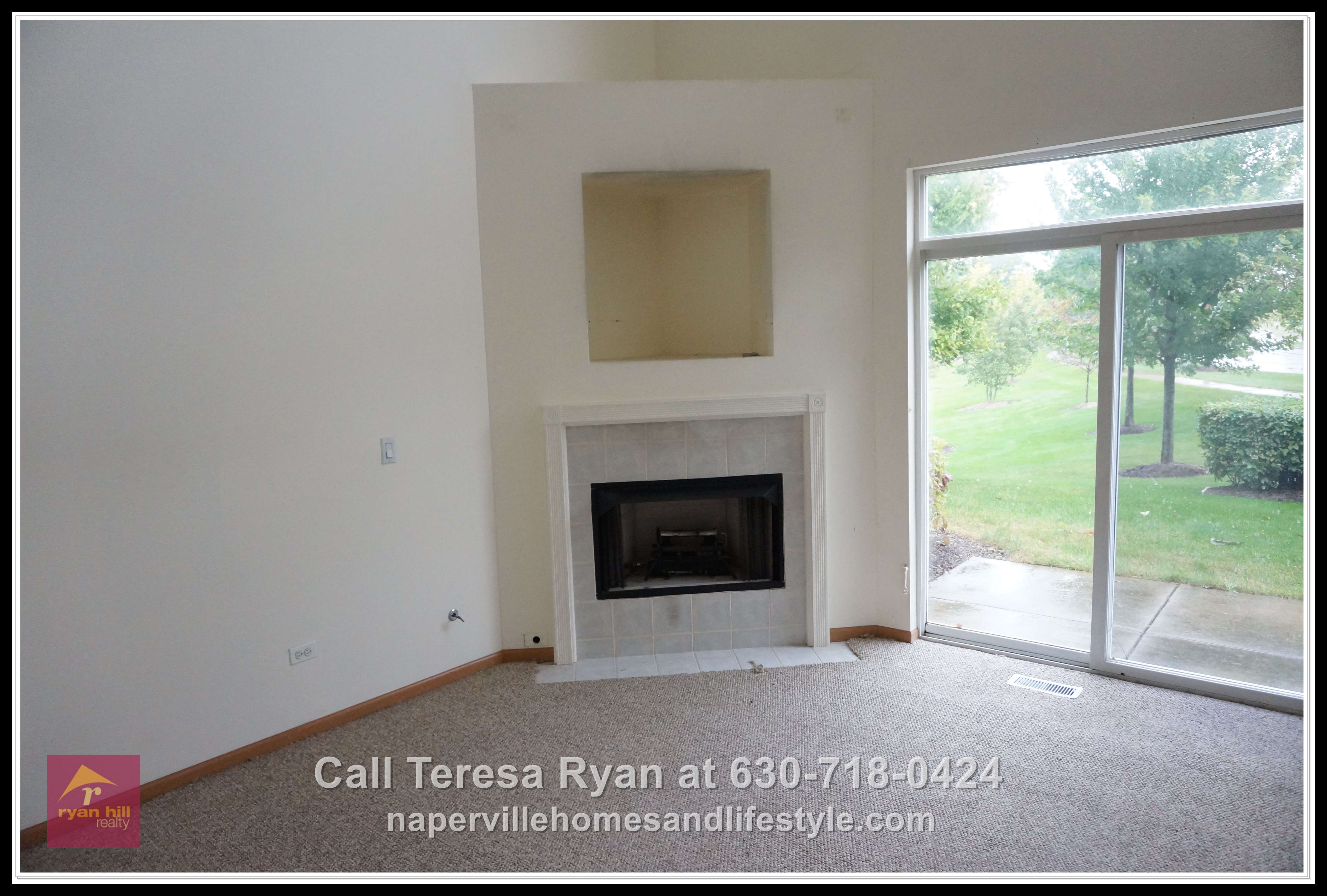 Homes for sale in Naperville IL - The living room with its gas fireplace and a stunning view of the water is cozy and comfy.