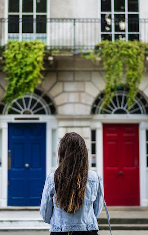 girl standing in front of two front doors